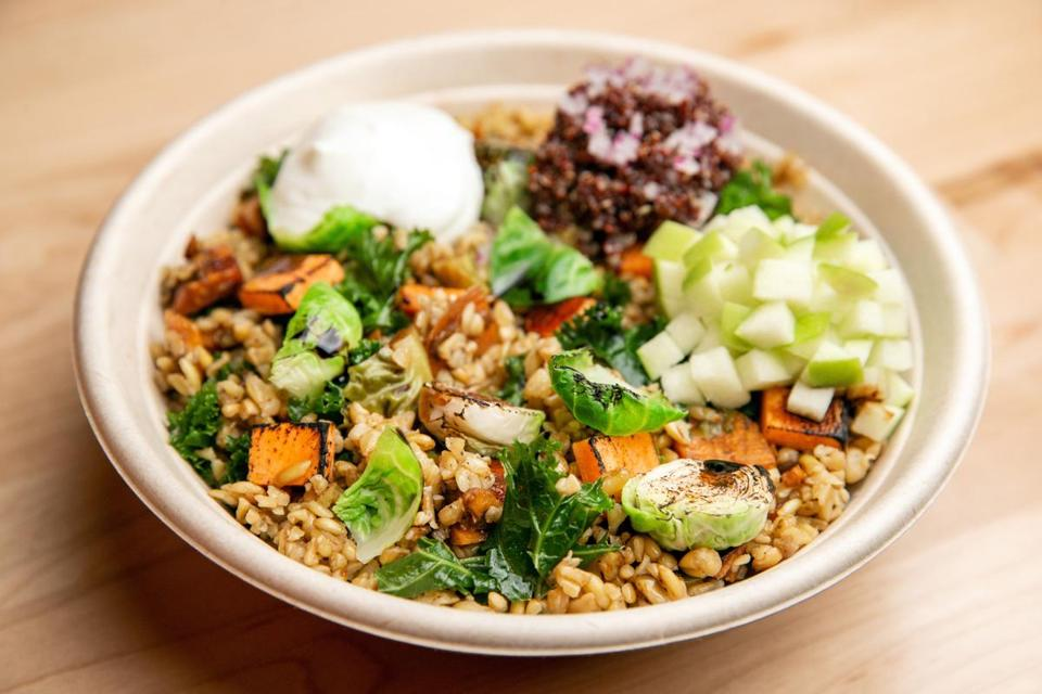 The Hearth bowl includes balsamic-glazed Brussels sprouts and sweet potatoes with kale, quinoa, and freekeh, topped with yogurt and chopped Granny Smith apples.